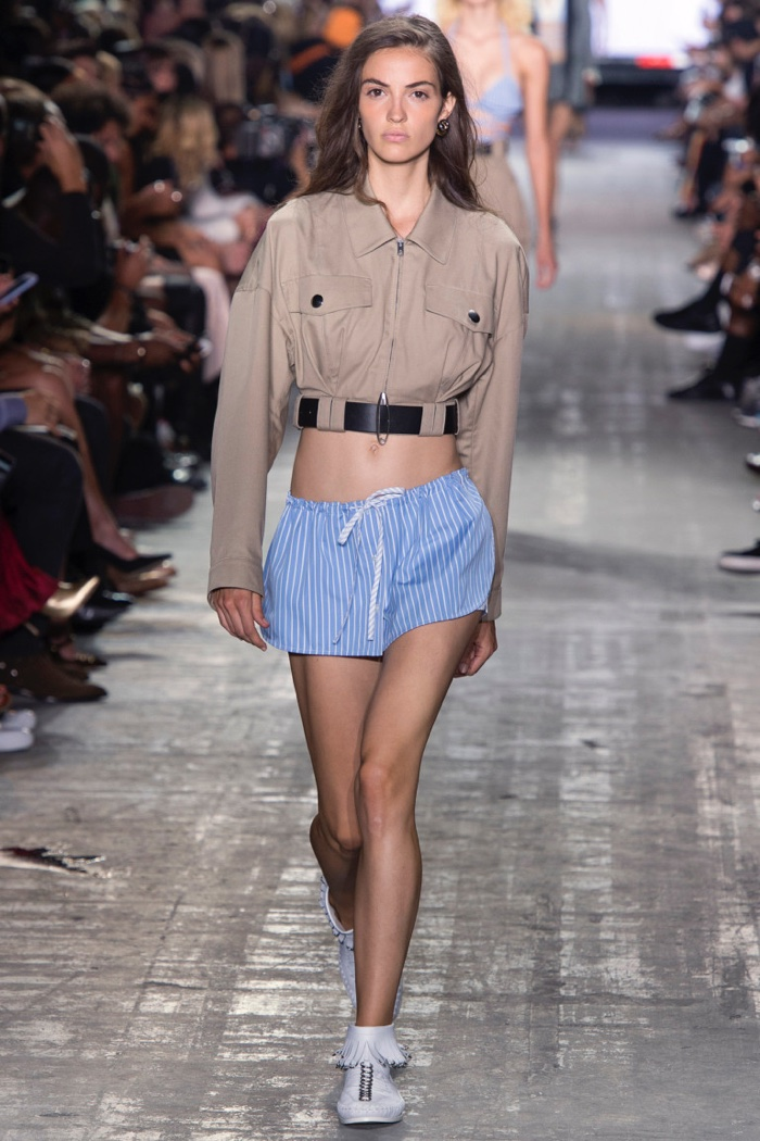 Alexander Wang Spring 2017: Model walks runway in cropped khaki jacket and striped pajama shorts with white fringed sneakers