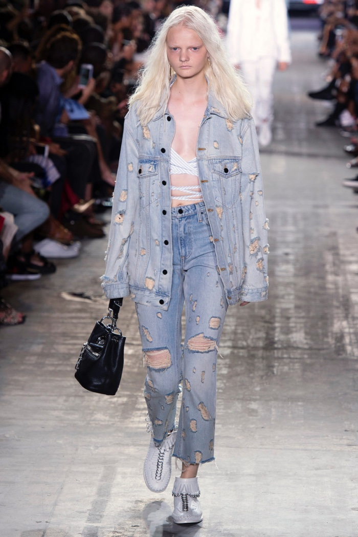 Alexander Wang Spring 2017: Model walks runway in distressed denim jacket and jeans with strappy top