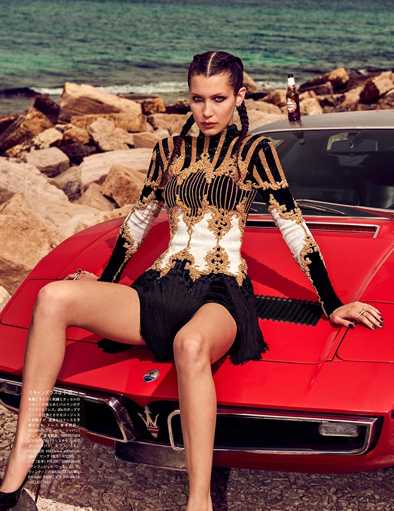 Sitting on top of a red car, Bella Hadid models a Balmain dress with embellished detail