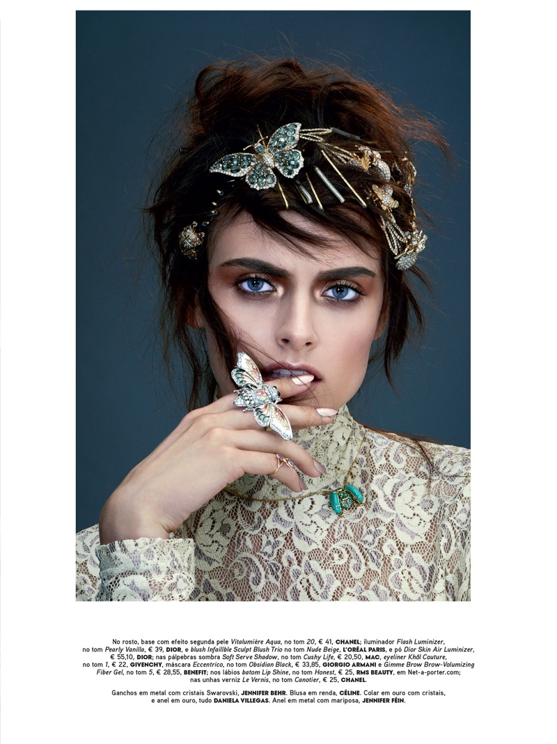 Model Zuzana Gregorova poses with bejeweled butterfly accessories and Celine lace blouse