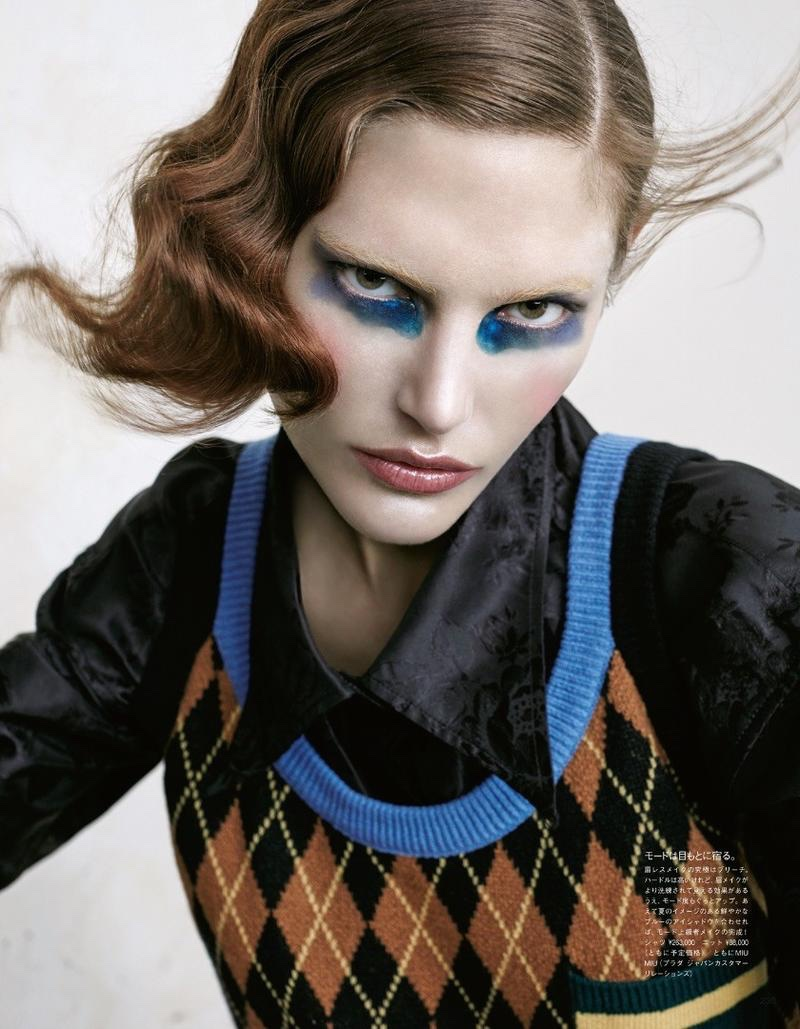 Catherine McNeil models blue eye makeup with black shirt and argyle sweater vest from Miu Miu