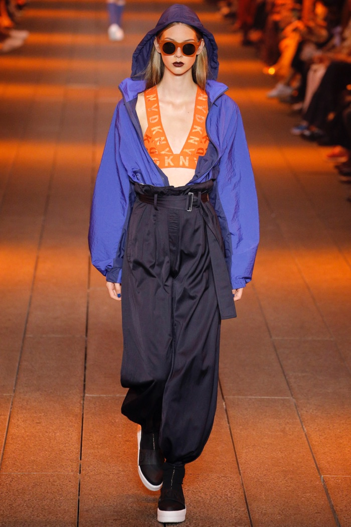 DKNY Spring 2017: Lauren de Graaf walks the runway in pilot blue and classic navy floaty nylon hooded jacket, orange logo bra top and classic navy sateen paper bag pant