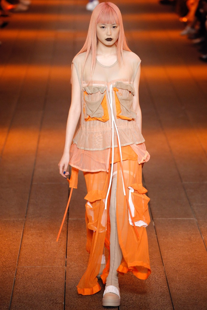 DKNY Spring 2017: Fernanda Ly walks the runway in taupe, pink and orange tulle pocket dress, pink logo bandeau and mesh litewear bike shorts