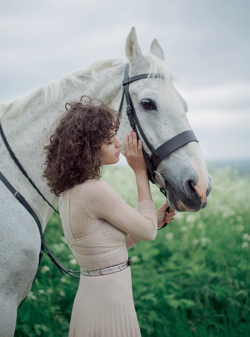 The model poses with a white horse