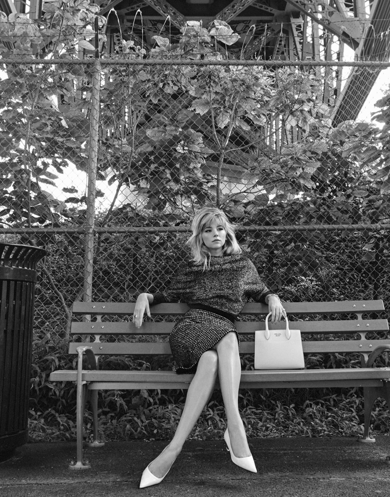 Sitting on a bench, Haley Bennett wears Jil Sander sweater, Dolce & Gabbana skirt with Marni pumps and Prada handbag