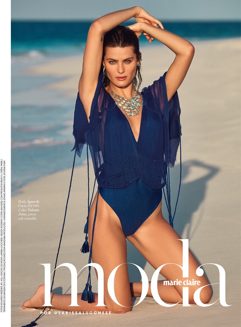 Isabeli Fontana poses by the sea in the fashion editorial featuring jewel tone looks