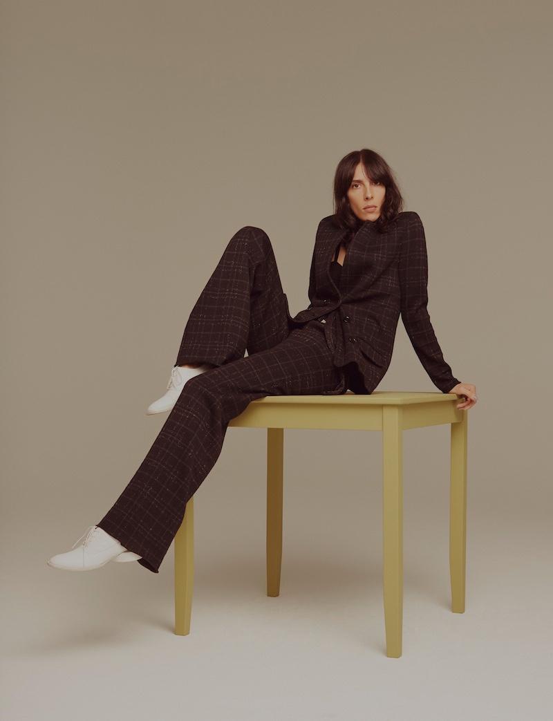 Posing on a table, Jamie Bochert wears Bottega Veneta jacket and pants with Jacquemus shoes