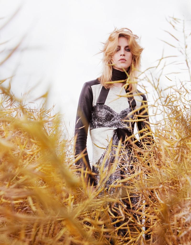 Posing in a golden field, the model wears a Louis Vuitton ensemble