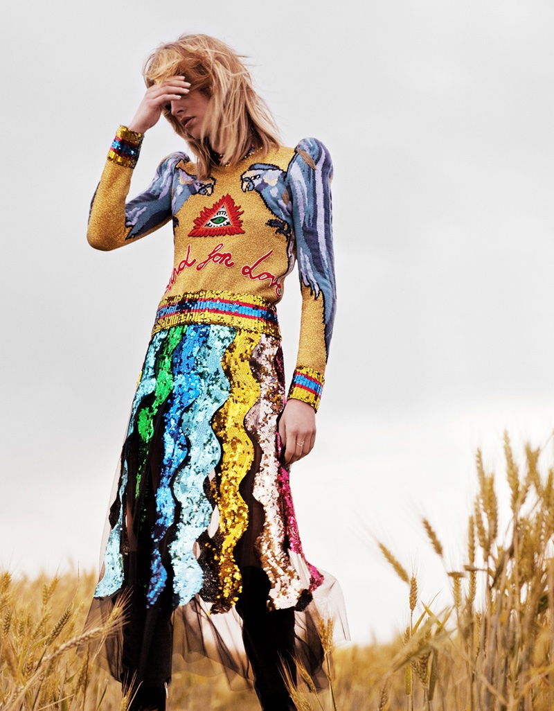 The model poses in Gucci pullover sweater with sequin embellished skirt