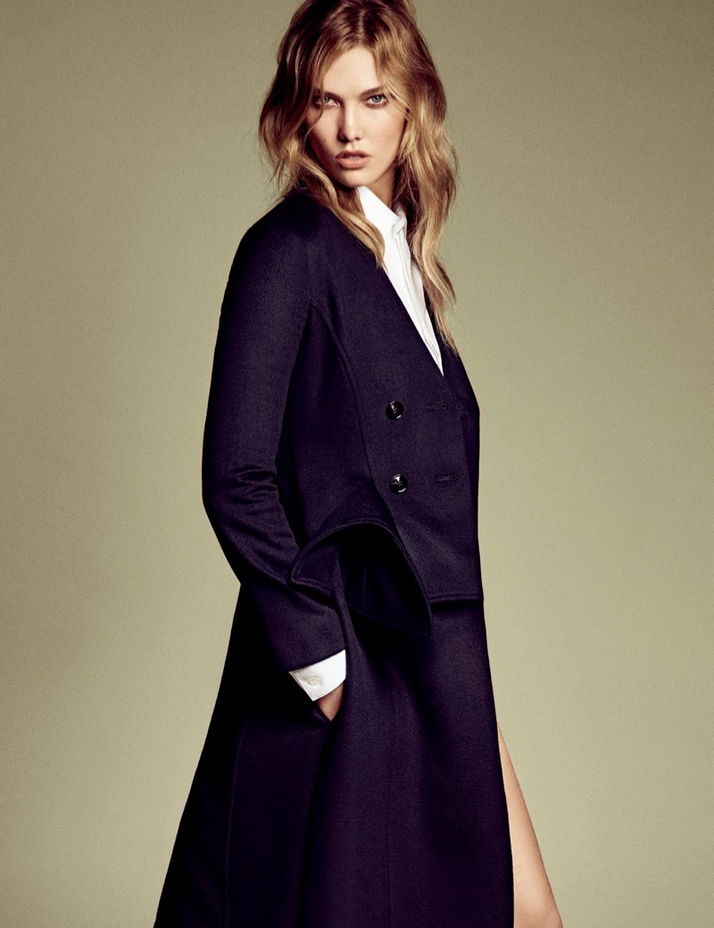 Karlie Kloss poses in black coat