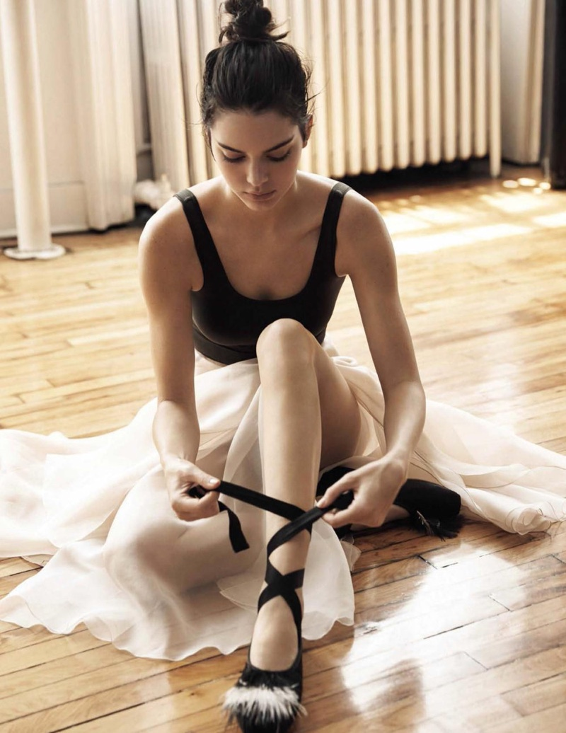 Kendall Jenner laces up ballerina flats in this image