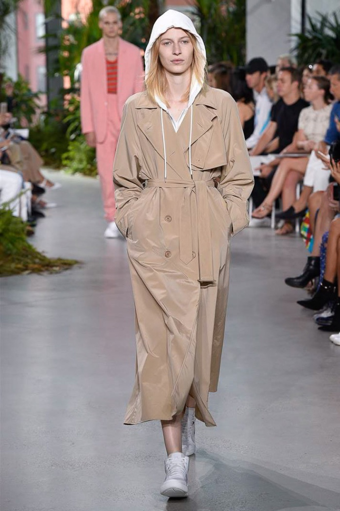 Lacoste Fall 2016: Julia Nobis walks the runway in tan trench coat over hooded sweatshirt and white sneakers