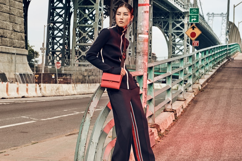 Liu Wen strikes a pose in sweater and pants by Cédric Charlier; earrings by Uribe with bag by Marni