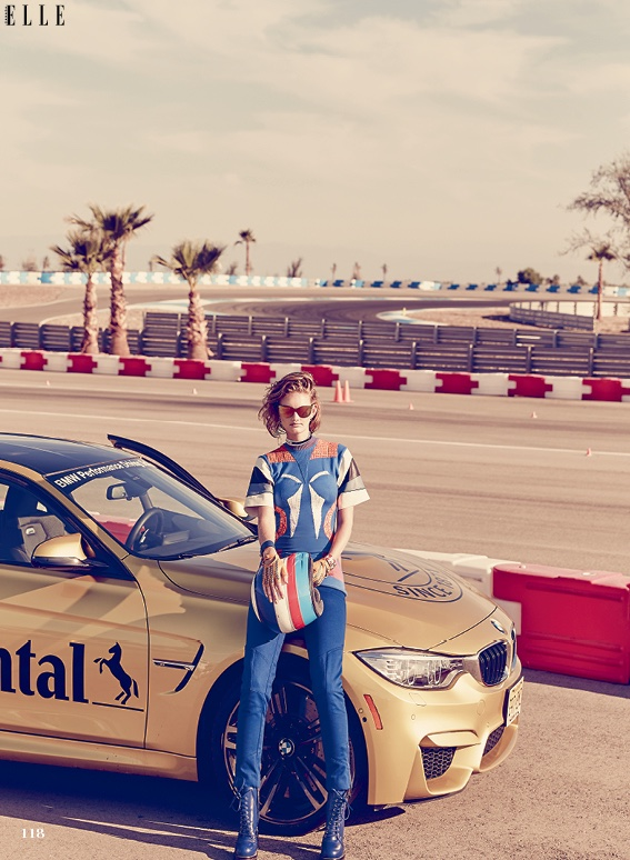 On the race track, Patricia van der Vliet models Louis Vuitton top and pants with leather boots