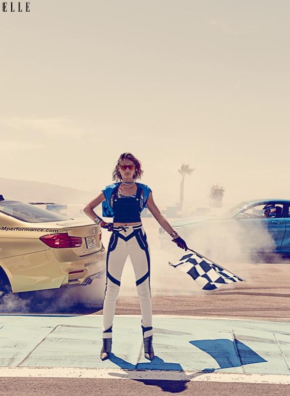 Holding a race flag, Patricia van der Vliet wears moto inspired look