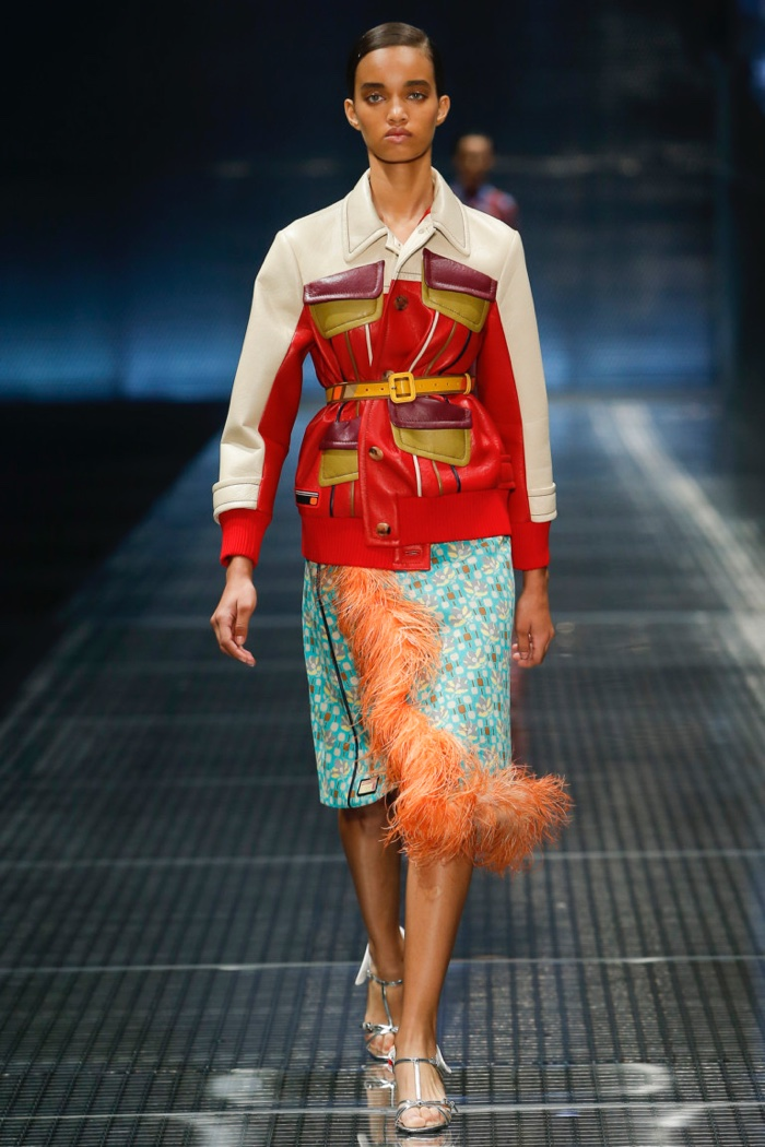 Prada Spring 2017: Model walks the runway in color-blocked leather jacket over feather-trimmed printed skirt