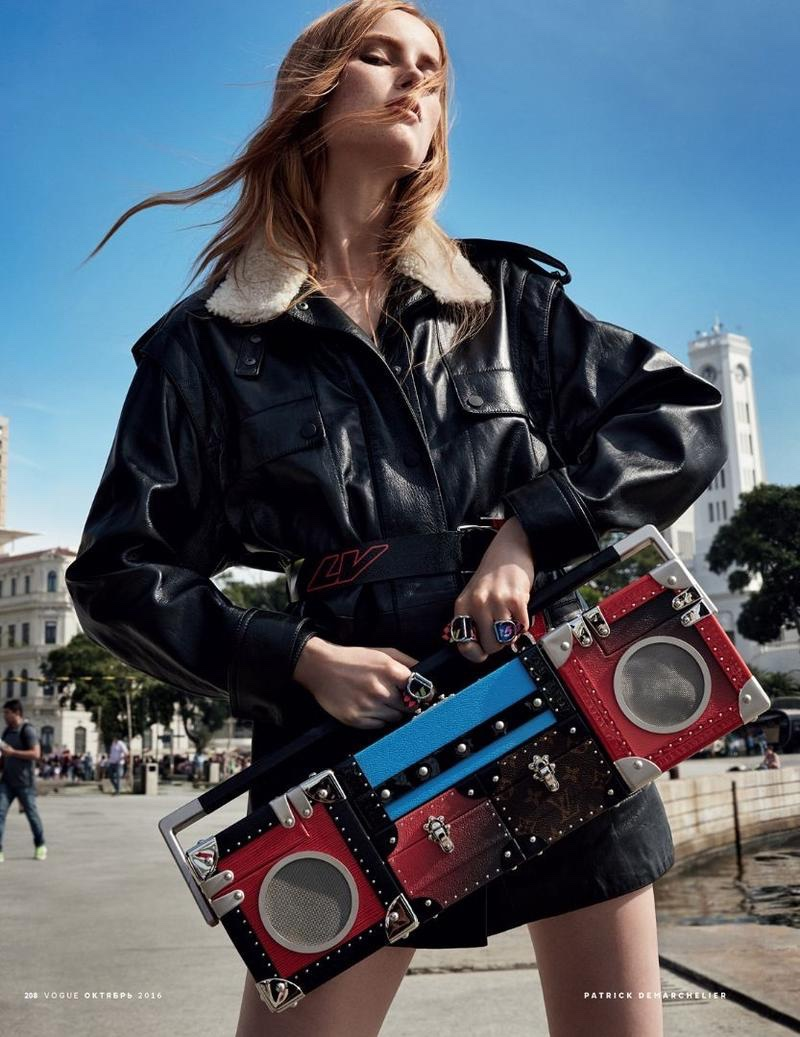 The model poses in Louis Vuitton leather jacket and boombox bag