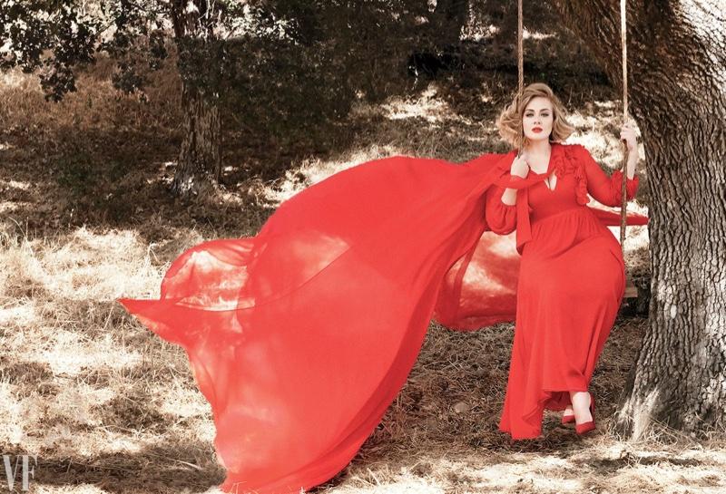 Posing under an oak tree, Adele wears a red cape and dress
