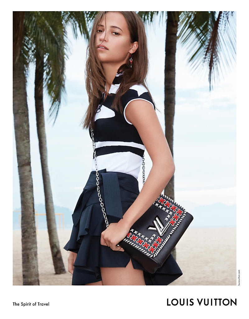 Against a backdrop of palm trees, Alicia Vikander wears Louis Vuitton Twist MM bag