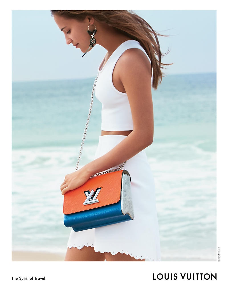 At the beach, Alicia Vikander poses with the Louis Vuitton Twist MM bag