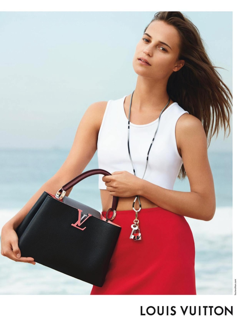 Posing at the beach, Alicia Vikander models the Louis Vuitton Capucines PM bag