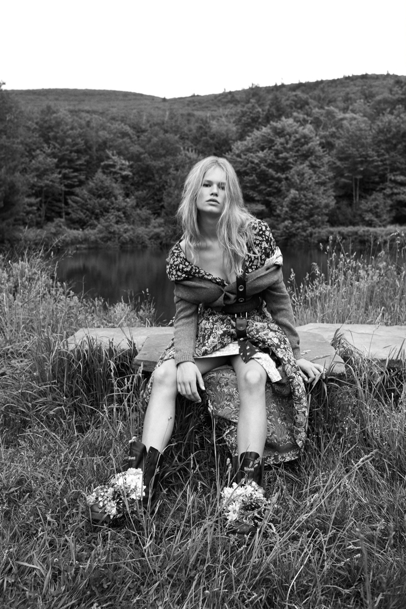 Posing outdoors, Anna Ewers models a cardigan and floral skirt from Miu Miu