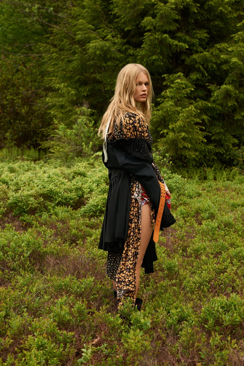 Surrounded in green, Anna Ewers poses in black blazer and kilt from DSquared2