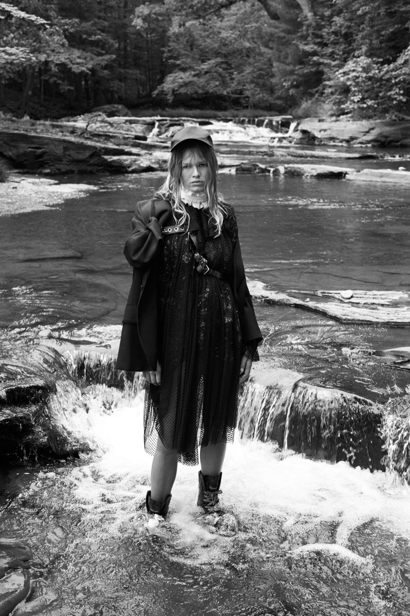 The model poses at a lake in the grunge inspired look