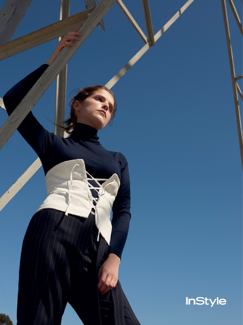 Anna Kendrick poses in turtleneck with corset and pinstriped pants