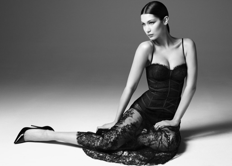 Photographed in black and white, Bella Hadid poses in a lace dress from Misha Collection