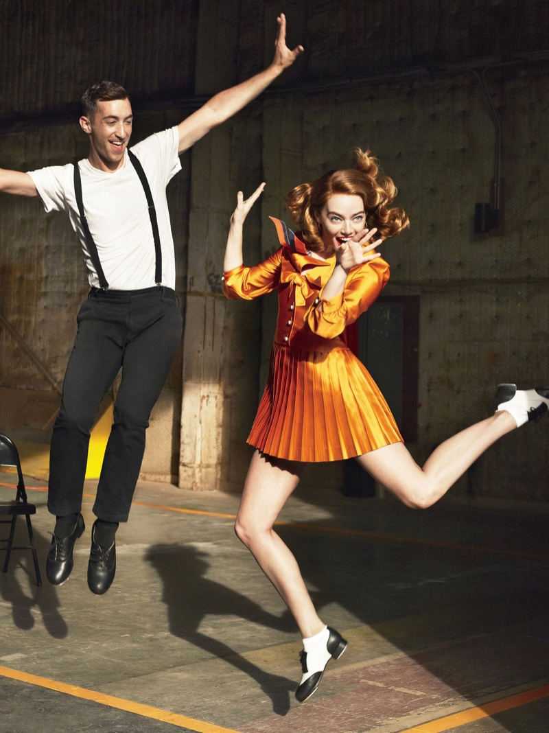 Taking a leap, Emma wears orange Gucci dress with pleating