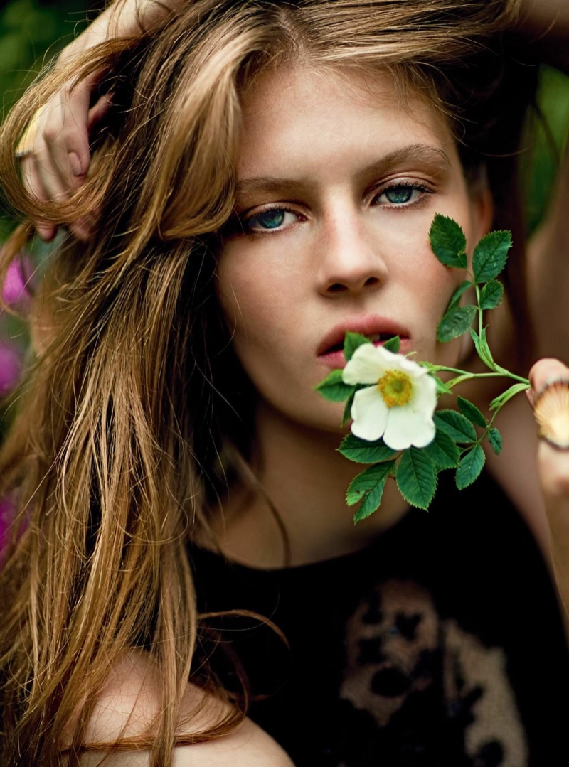 Posing with a flower, Florence Kosky wears a messy hairstyle
