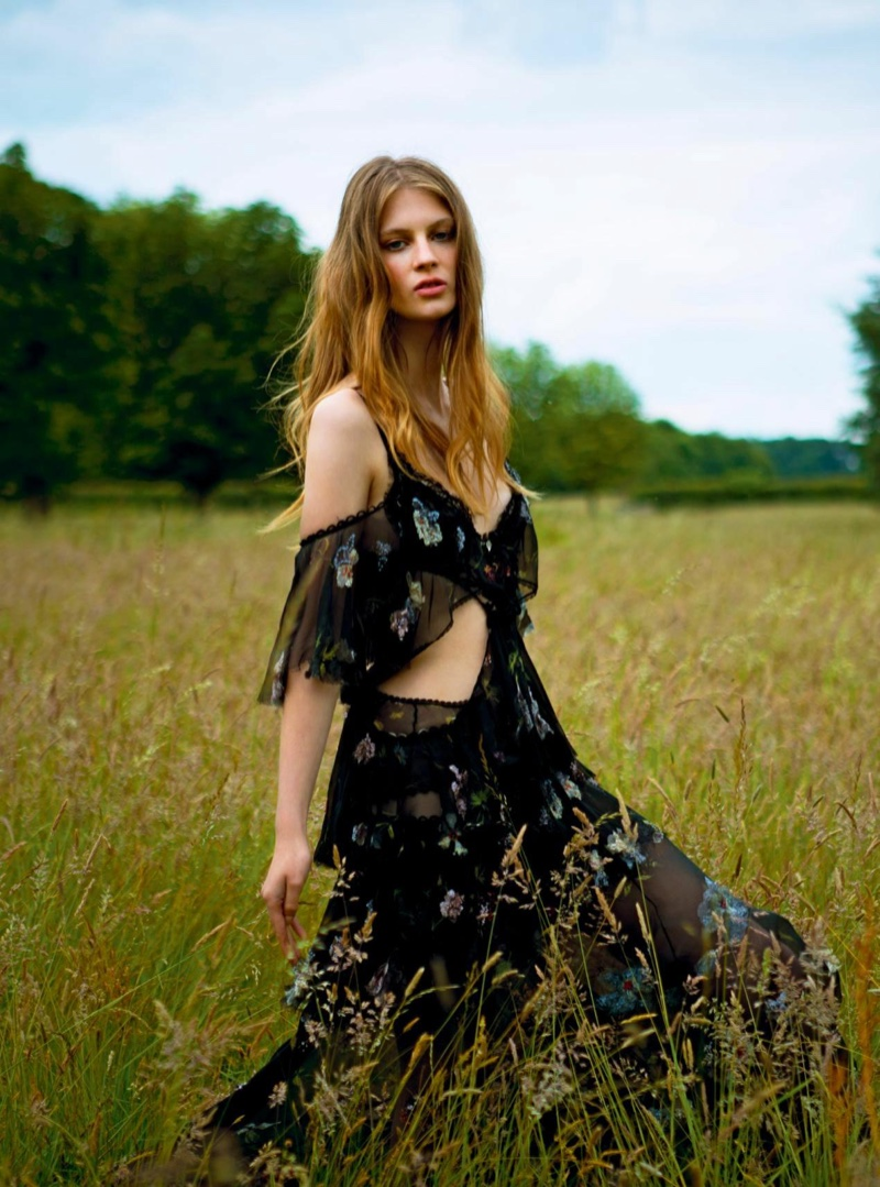 Posing outdoors, Florence Kosky wears off-the-shoulder gown from Alexander McQueen