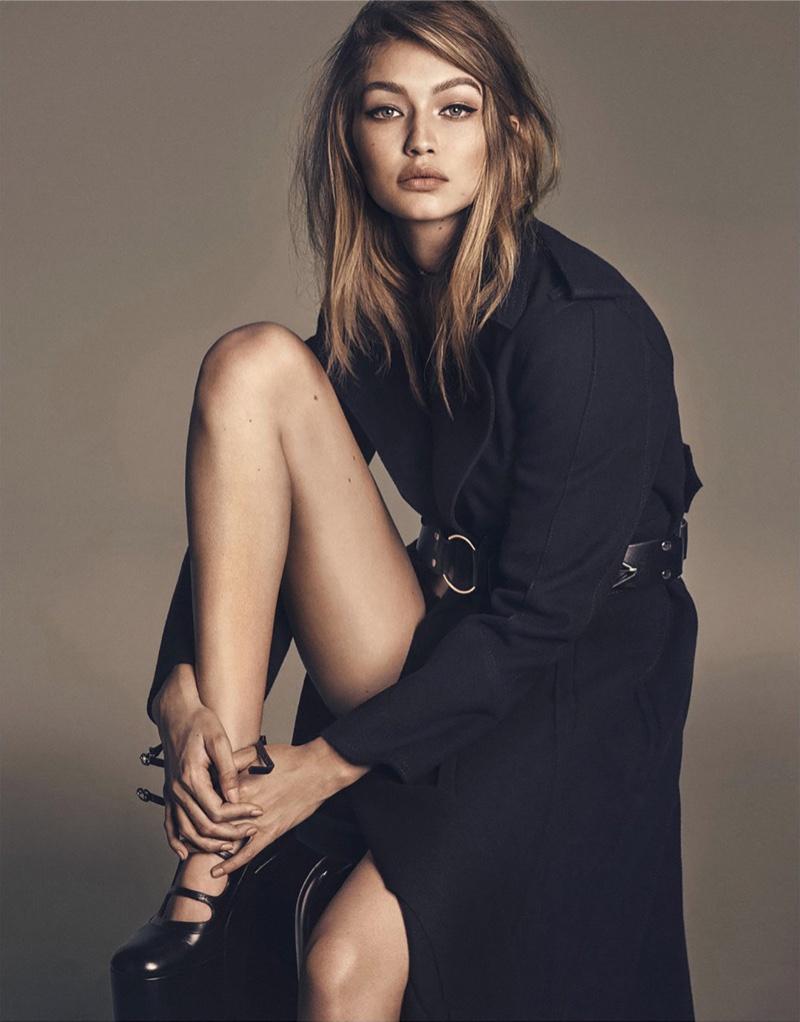 Flaunting some leg, Gigi Hadid models black trench coat