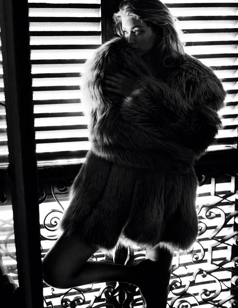 Photographed in black and white, Gigi Hadid models fur coat