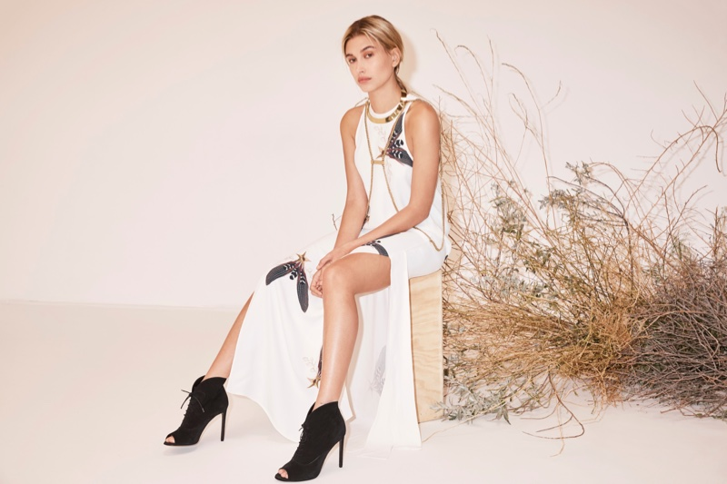 Model Hailey Baldwin poses in embellished white dress from Sass & Bide's resort collection