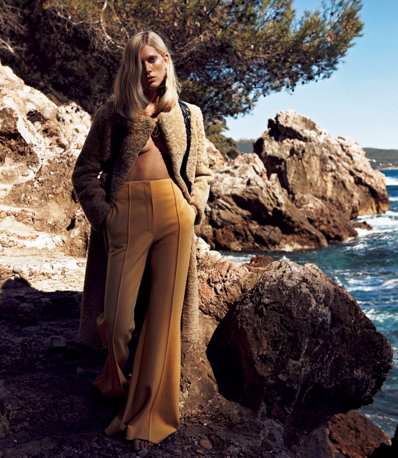 Model Iselin Steiro poses in Celine coat and wide-leg trousers