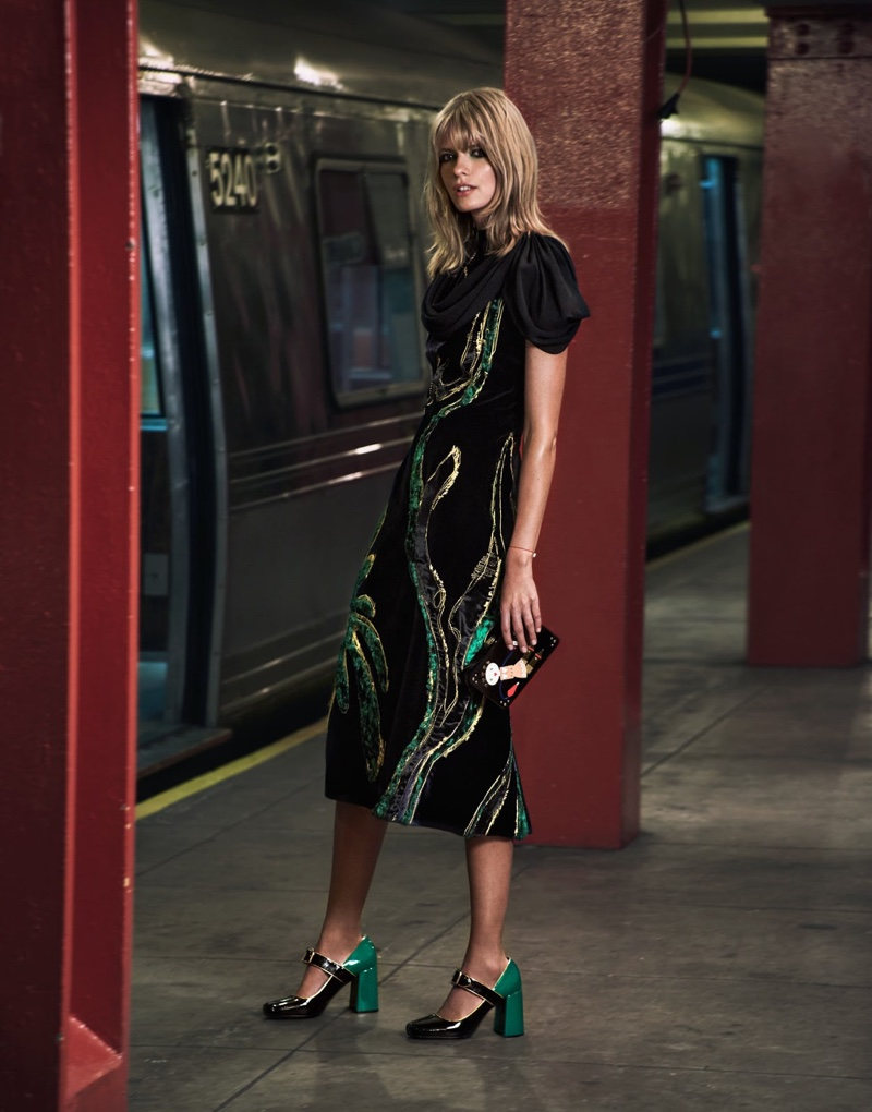 Standing on a subway platform, the model wears a Prada dress, clutch and block heel pumps