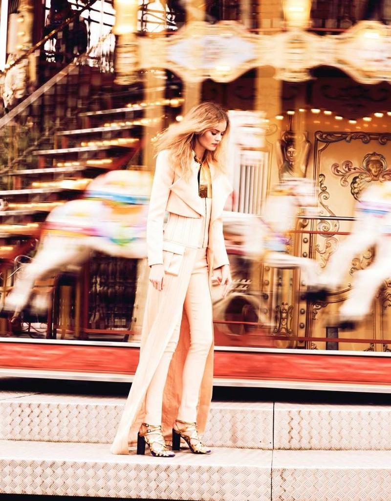 Posing by a carousel, Kate Grigorieva wears Balmain coat, top and pants