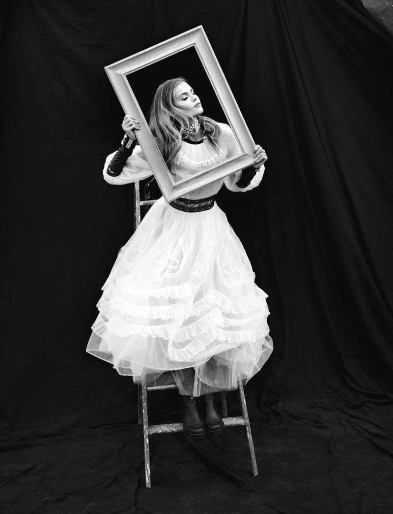 Posing with a frame, the model wears a white Chanel dress and boots