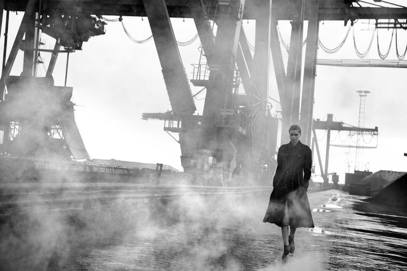 Walking through a smokey scene, Lara Stone wears a long coat
