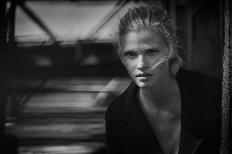 Model Lara Stone poses in a dark wardrobe for the fashion editorial
