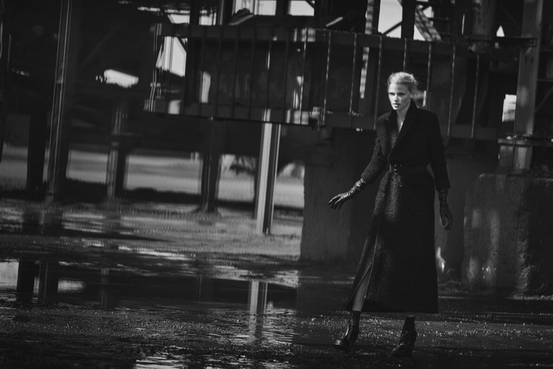 Covering up in a tailored coat and leather gloves, Lara Stone poses in an industrial scene