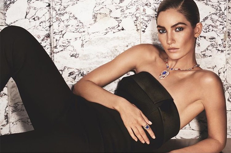 Model Lily Aldridge lounges in black jumpsuit with Bulgari jewels