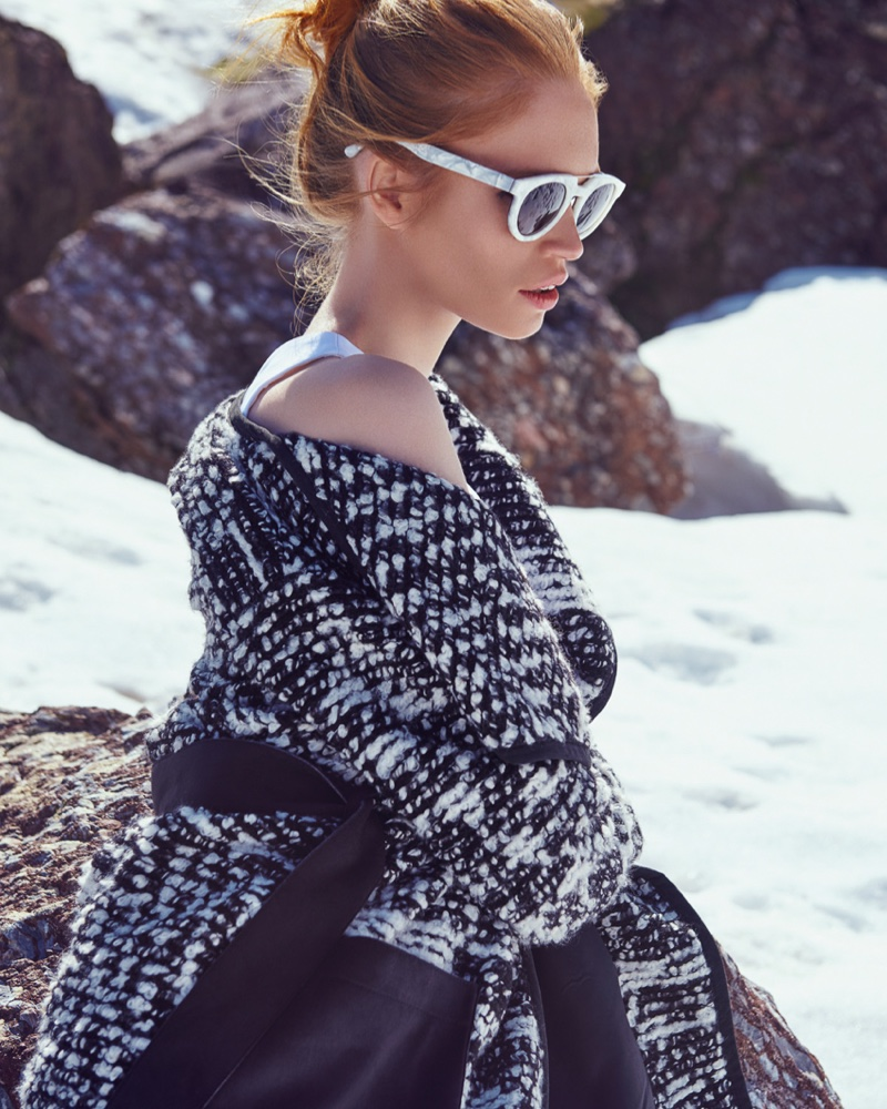 The redhead model cozies up in a knit piece