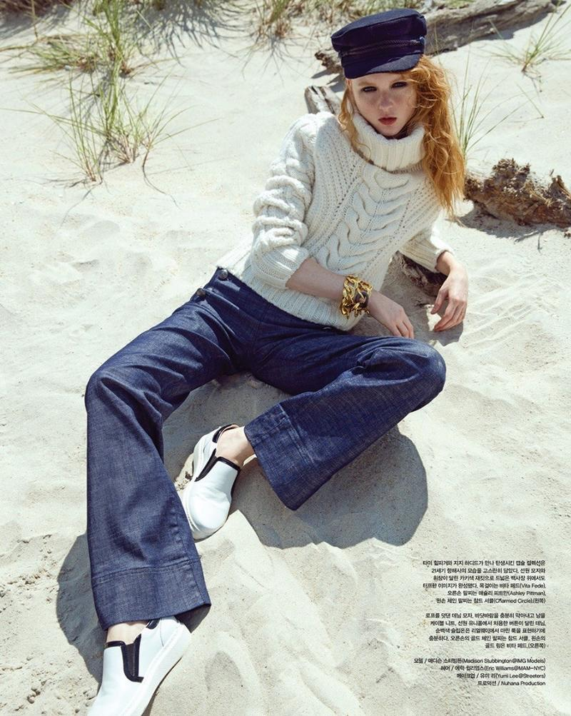 Laying on the sand, Madison Stubbington wears Gigi Hadid x Tommy Hilfiger cable knit sweater and flared denim