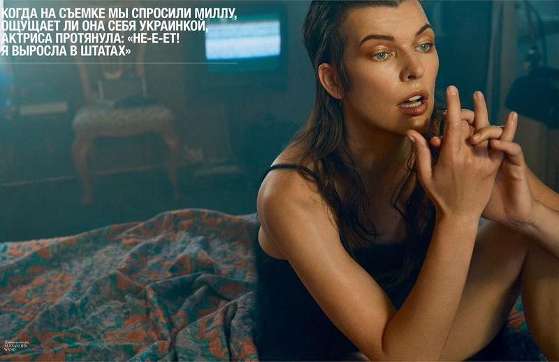 Posing on a bed, Milla Jovovich wears Alexander Wang dress