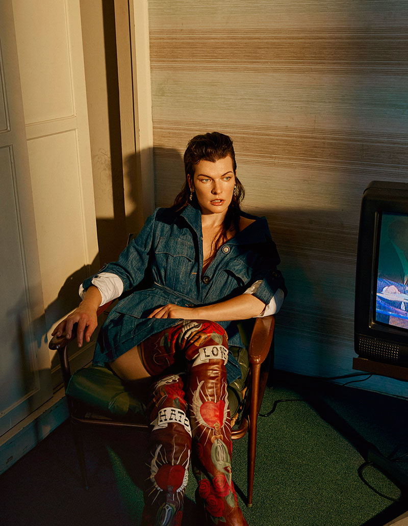 Sitting in a chair, Milla Jovovich wears Miu Miu denim jacket with embroidered Vetements boots