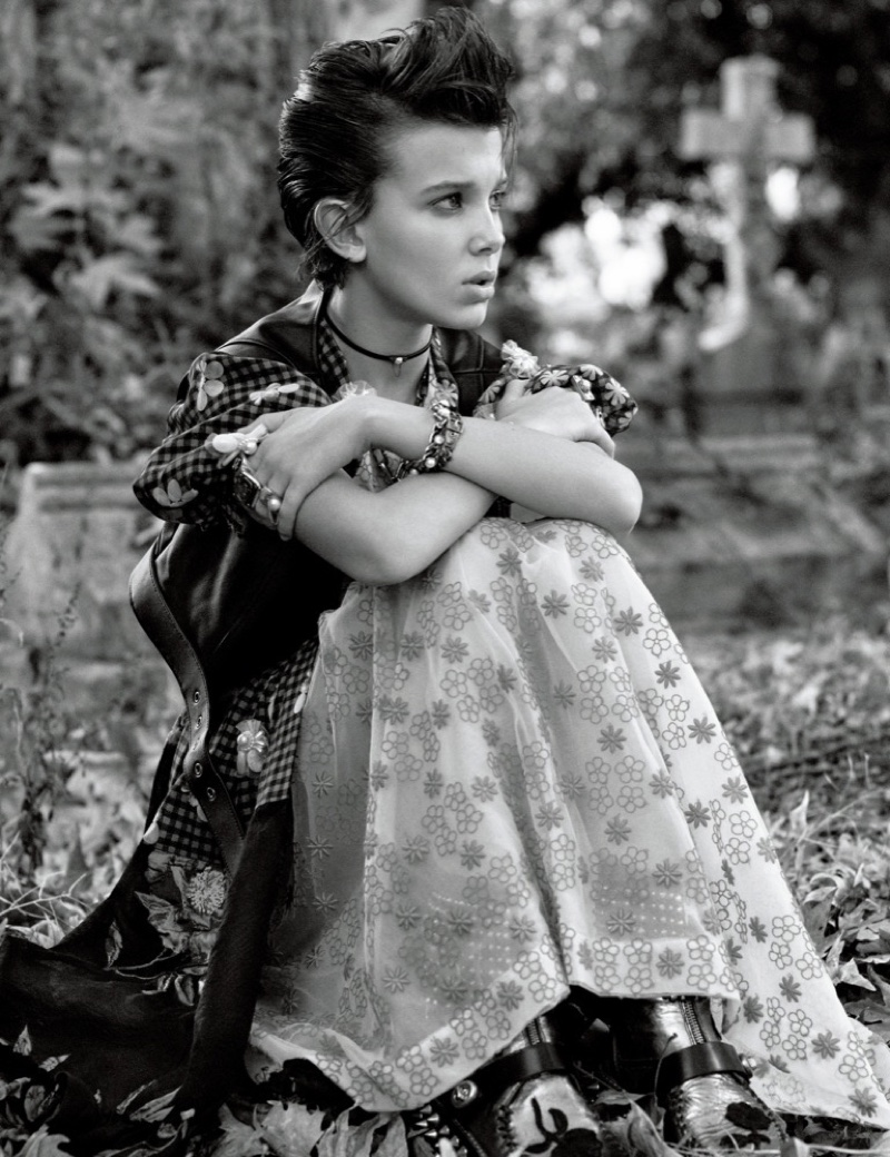 Sitting on grass, Millie Bobby Brown wears Coach vest with Simone Rocha dress