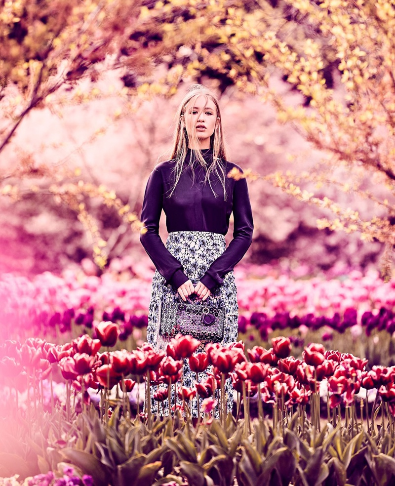Posing in the Tulip Top Gardens, Natalia Siam wears Dior shirt, skirt and bag